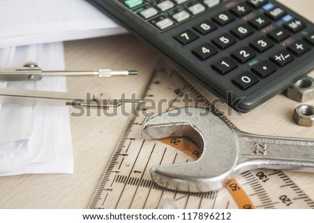 drawing tools with wrench and calculator over wood table
