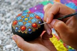 Drawing with a brush a dot mandala on a stone