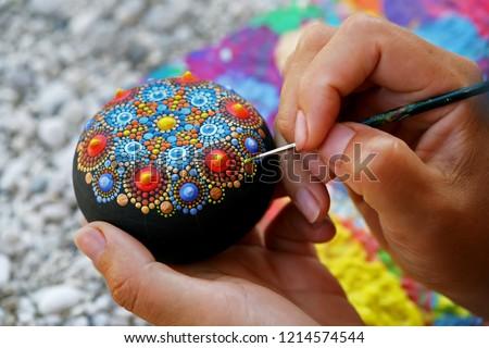 Drawing with a brush a dot mandala on a stone Stock photo ©