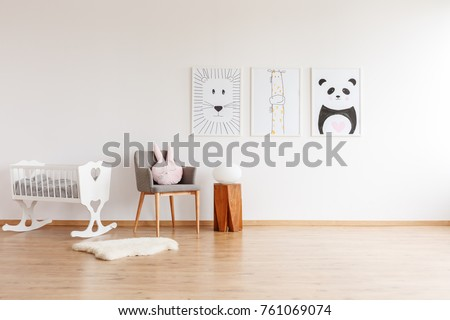 Drawings on white wall above grey chair with pillow and wooden stool in baby\'s room with white crib and rug
