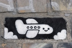 Drawn black and white airplane with a smile on a brick wall.
