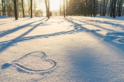 Drawn heart in a snow landscape.Winter evening sunset nice background.