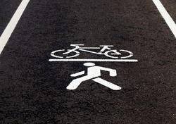 drawn symbol of a Bicycle and pedestrian on the territory of a combined bike path and road for pedestrians, closeup