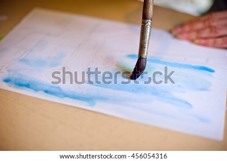 Draws the brush on the paper blue, watercolor