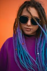 Dread hair girl. Girl on an orange background. Blue hair dread. Dread hair woman. Blue hair woman. Woman on an orange background.