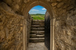 dream and final goal fairy tale concept colorful picture of big world view from narrow arch shape entrance of medieval castle dungeon