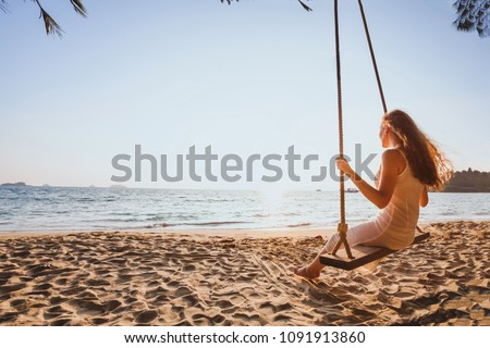 dream and happiness concept, romantic beautiful carefree woman relaxing on the swing at sunset beach, summer holidays, vacation travel and relaxation, inspiring landscape