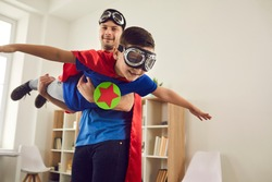 Dream big. Loving father helps his son fly like a superhero. Boy with pilot glasses play fly with his dad at home. Cheerful family in red cloaks and pilot glasses are having fun together.