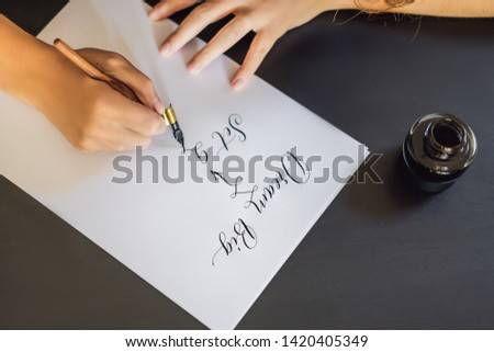 dream big set goals take action. Calligrapher Young Woman writes phrase on white paper. Inscribing ornamental decorated letters. Calligraphy, graphic design, lettering, handwriting, creation concept #1420405349