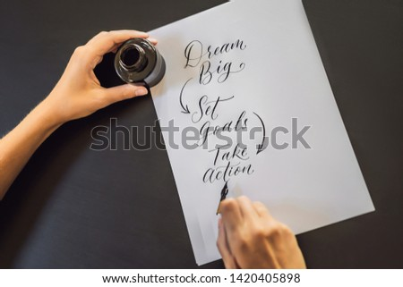 dream big set goals take action. Calligrapher Young Woman writes phrase on white paper. Inscribing ornamental decorated letters. Calligraphy, graphic design, lettering, handwriting, creation concept