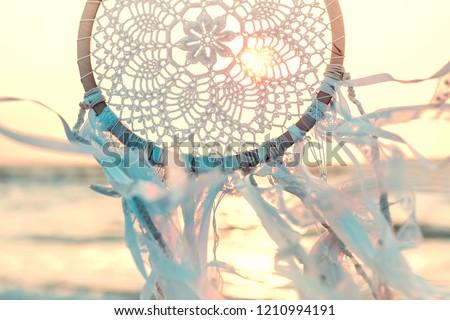 Dream catcher against sunrise. Handmade work is ethnic symbol. #1210994191