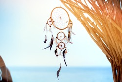 Dream catcher boho style blown around by a light sea breeze. Beach bar interior detail.