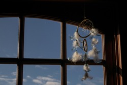 dream catcher by a window with blue sky and sun light