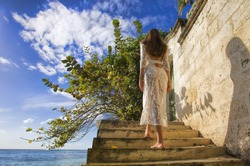 Dream island bride who goes into summer in her gorgeous lace white wedding dress, barefoot, on the beautiful stone steps by the Caribbean sea on the island of Barbados