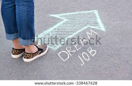 Dream job concept. Female feet and drawing arrow on pavement background