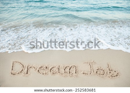 Dream Job written on sand by sea at beach