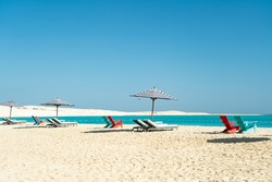 Dream paradise beach with umbrellas and chairs at the turquoise Mediterranean sea at El Alamein near Alexandria, Egypt
