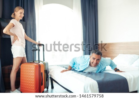 Dream vacation. Smiling married couple being happy finaly relaxing in their new hotel room. #1461579758