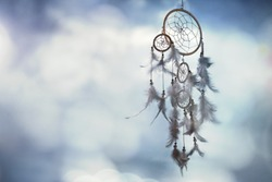 Dreamcatcher on blue background with copy space