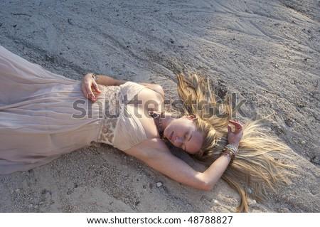 Dreamer. Feminine aspect. Woman lying in dry river run in a beautiful gown.