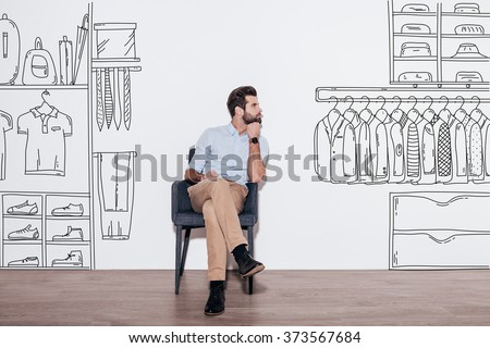 Shutterstock Dreaming about new wardrobe. Young handsome man keeping hand on chin and looking away while sitting in the chair against illustration of closet in the background