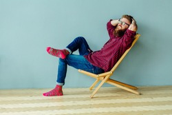 Dreaming about vacation concept. Studo shot of man resting on a chair over gray wall at home.