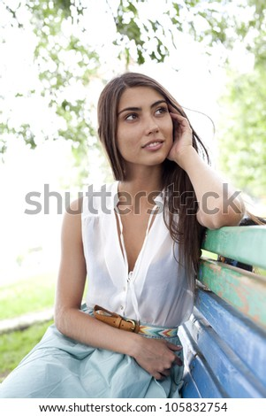dreaming attractive young white girl posing outdoors in a bright sunny summer day