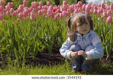 Dreaming beautiful little girl in pink tulips