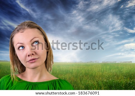 Dreaming beautiful young woman against summer landscape