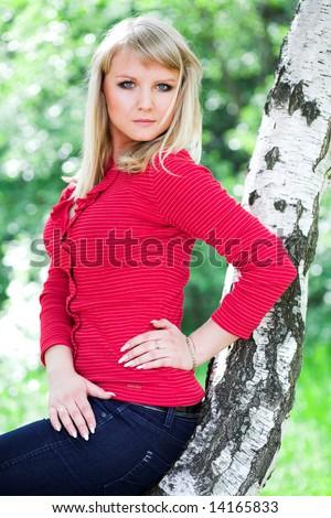 Dreaming girl in red near birch in park