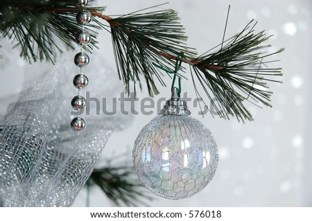 Dreaming of a White Christmas - Winter pine tree with silver holiday beads and iridescent wire covered balls hanging from the branches against a glistening, snow white background.