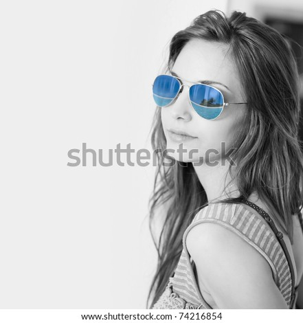 Dreaming of summer, black and white shot beautiful young brunette with tropical beach scene reflecting in her sunglasses.