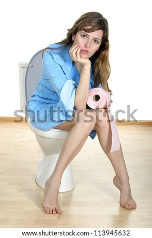 Dreaming on a toilet. Young woman sit on a toilet with toilet paper roll in her hand.