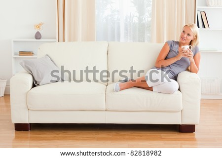 Dreaming woman holding a cup of coffee in her living room