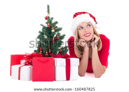 Dreaming woman lying down with christmas tree and gifts isolated on white background