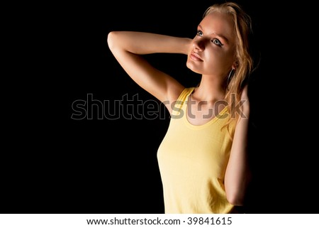 dreaming young pretty sensual blonde in yellow shirt looking up and relaxing isolated on black background with copy paste space