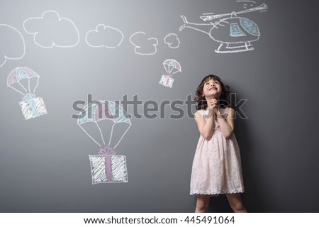 Dreams come true for the baby. Little girl is happy to receive presents on parachutes from the helicopter depicted with chalk on the neutral background.