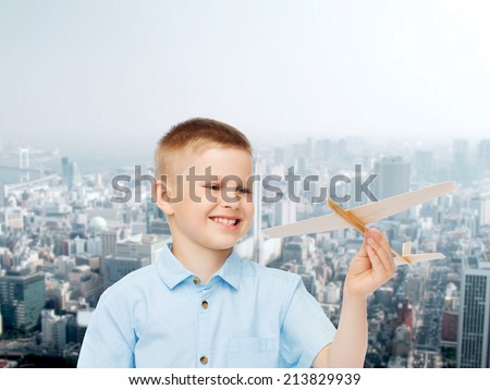 dreams, future, hobby, urban life and childhood concept - smiling little boy holding wooden airplane model in his hand over city background