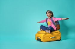 Dreams of travel! Child flying on a suitcase on background of bright blue wall.