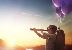 Dreams of travel! Child flying on balloons against the backdrop of a sunset.