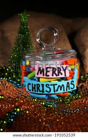 Dreams written on color  rolled paper in glass jar, on sackcloth and fabric background