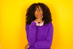 Dreamy African American female with pleasant expression, wearing casual clothes, looks sideways, keeps hand under chin, thinks about something pleasant, poses against yellow background.