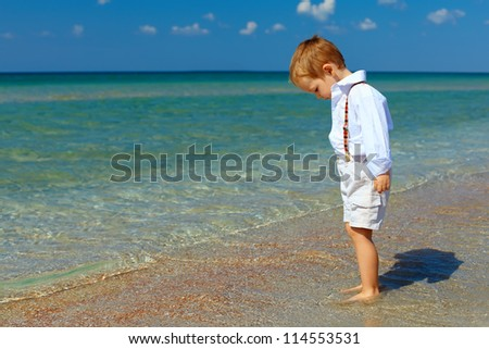 dreamy baby boy stands in surf on sea beach