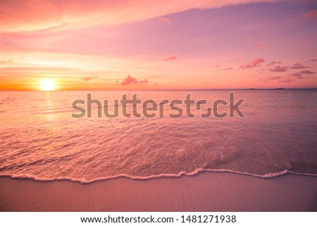 Dreamy beach scene with stunning waves. Colorful ocean beach sunrise or sunset, colorful bright sky and sun rays. Inspirational shoreline with soft tropical waves and relaxing mood. Peaceful, serene