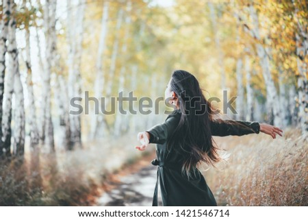 Dreamy beautiful girl with long natural black hair flies on bokeh background of autumn yellow leaves. Autumn euphoria in faded tones. Inspired emotional girl enjoys nature in fall forest. Back view.