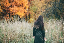 Dreamy beautiful girl with long natural black hair on background with colorful leaves. Fallen leaves in girl hands in autumn forest. Girl surrounded by vivid foliage. Back view. No face.