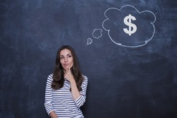 Dreamy beautiful woman with black hair standing near blackboard with dollar signs on it. Concept of money management