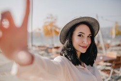 Dreamy brunette girl with short hair expressing happy emotions while making selfie outdoor. Photo of elegant young woman in hat and blouse taking picture of herself on blur background.