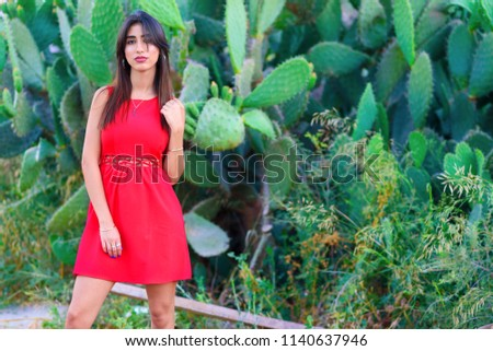 0d82c40fc5 Dreamy brunette young woman standing in cacti park wearing fashioned red  dress.Stylish trendy beautiful