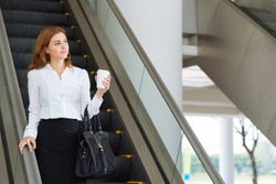 Dreamy businesswoman going down the escalator in office building